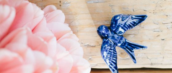Flores e andorinha sobre mesa de madeira