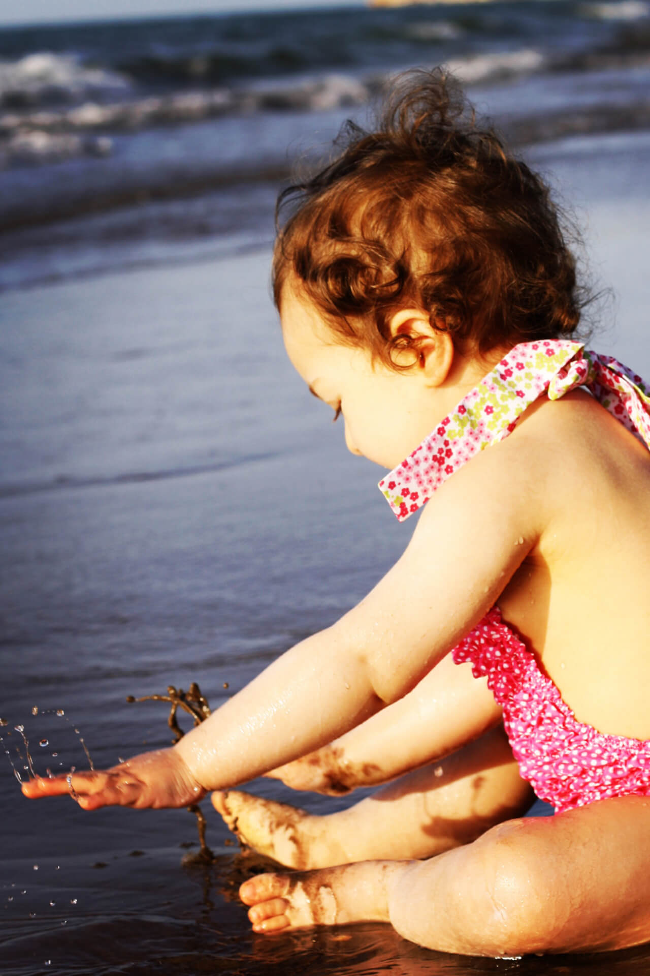 Bebé a brincar na praia, a chapinhar na água.