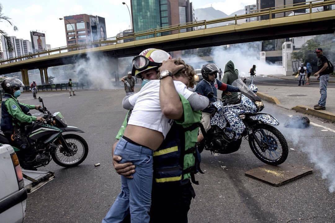 Homem com criança do colo nas manifestações da Venezuela.