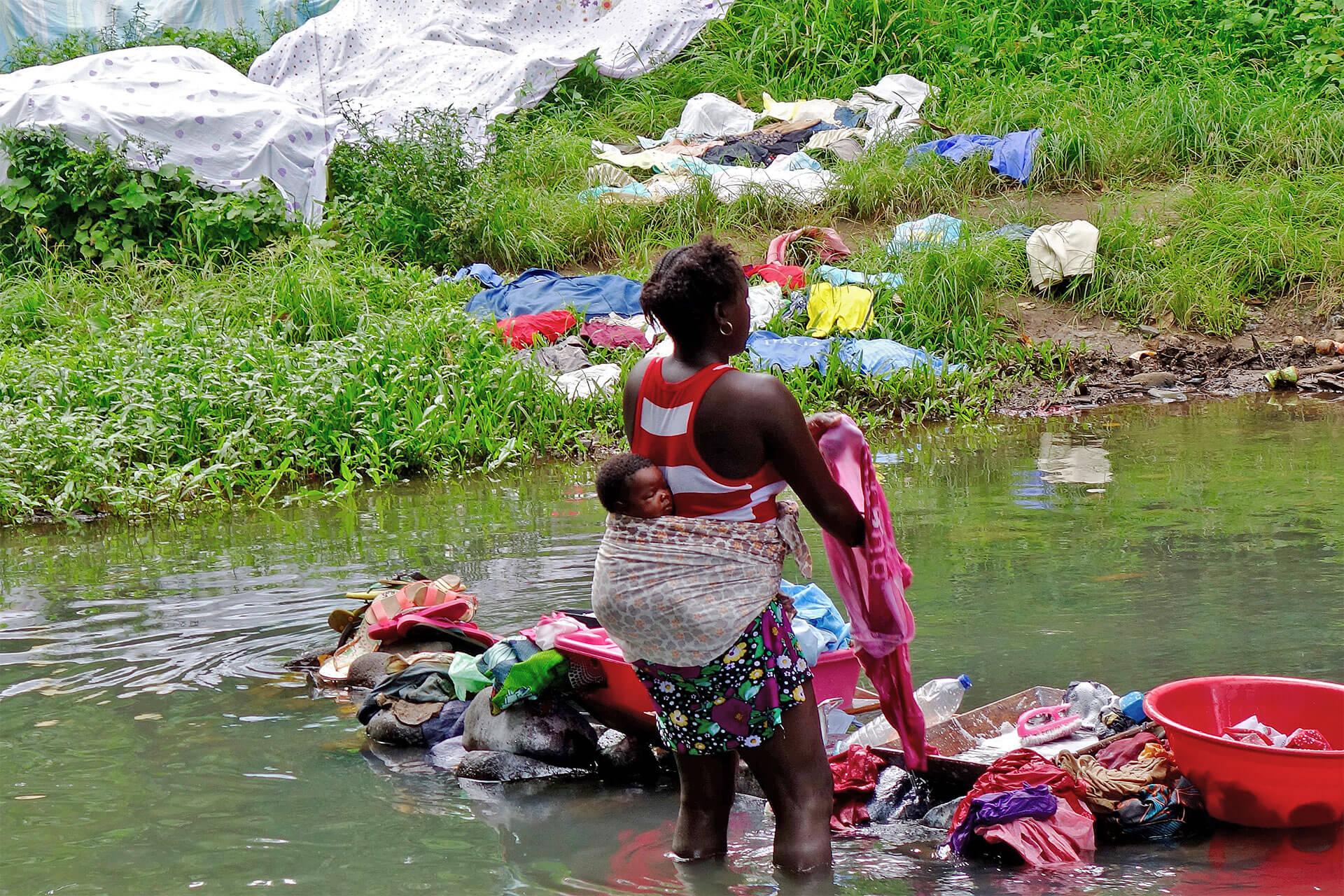 Uma mulher, com uma criança às costas, que lava a sua roupa no meio de um rio, é um bom exemplo na simplicidade das metas que nasce das intenções.