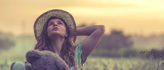 Rapariga com urso de peluche no campo, pelo pôr-do-sol