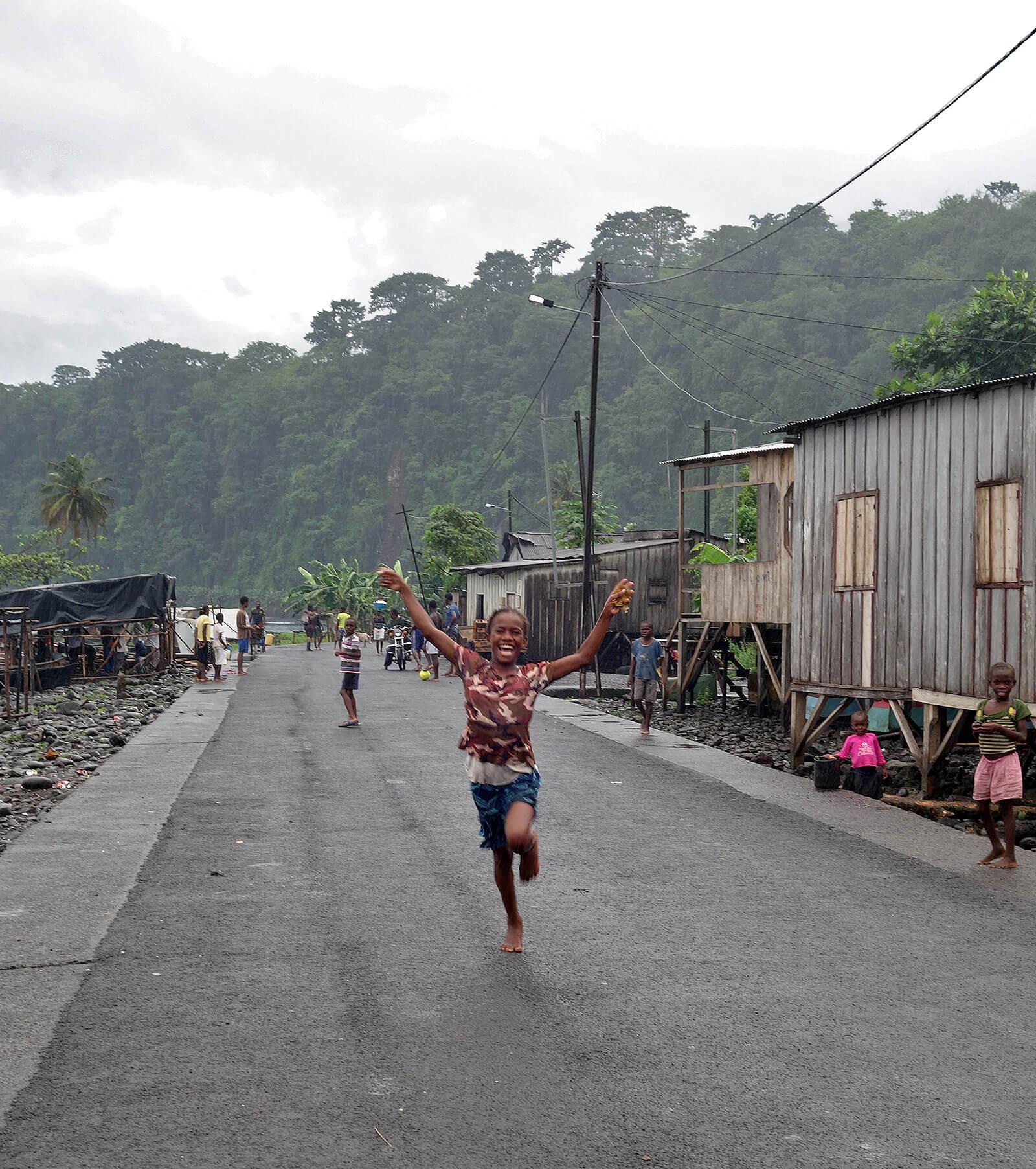 Criança africana a correr numa estrada, com casas de madeira laterais.