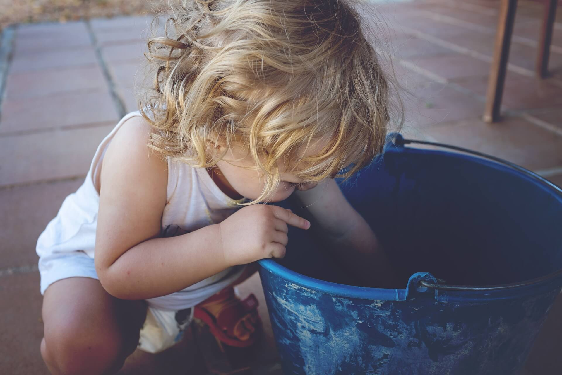 Criança loura a brincar com um balde azul sobre um pavimento de tijoleira.