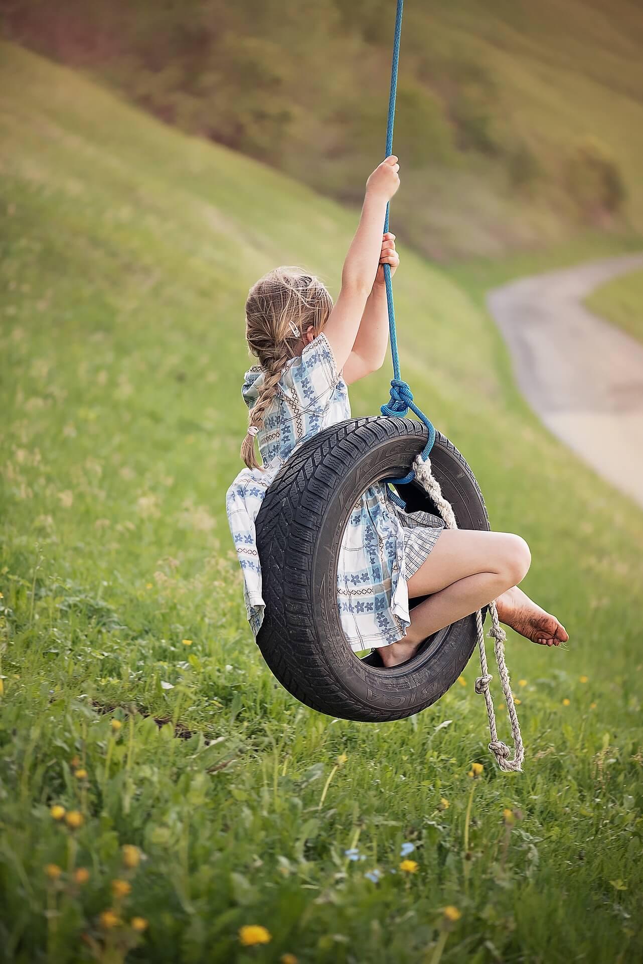 Menina a balouçar num pneu pendurado por uma corda, sobre um campo verde.