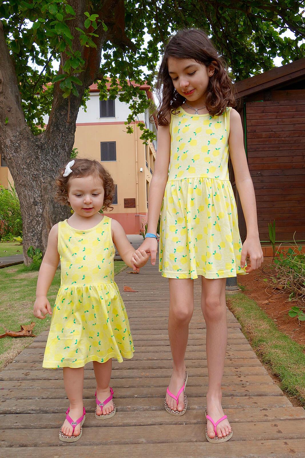 Meninas de vestido amarelo a caminharem de mãos dadas sobre um passadiço de madeira.