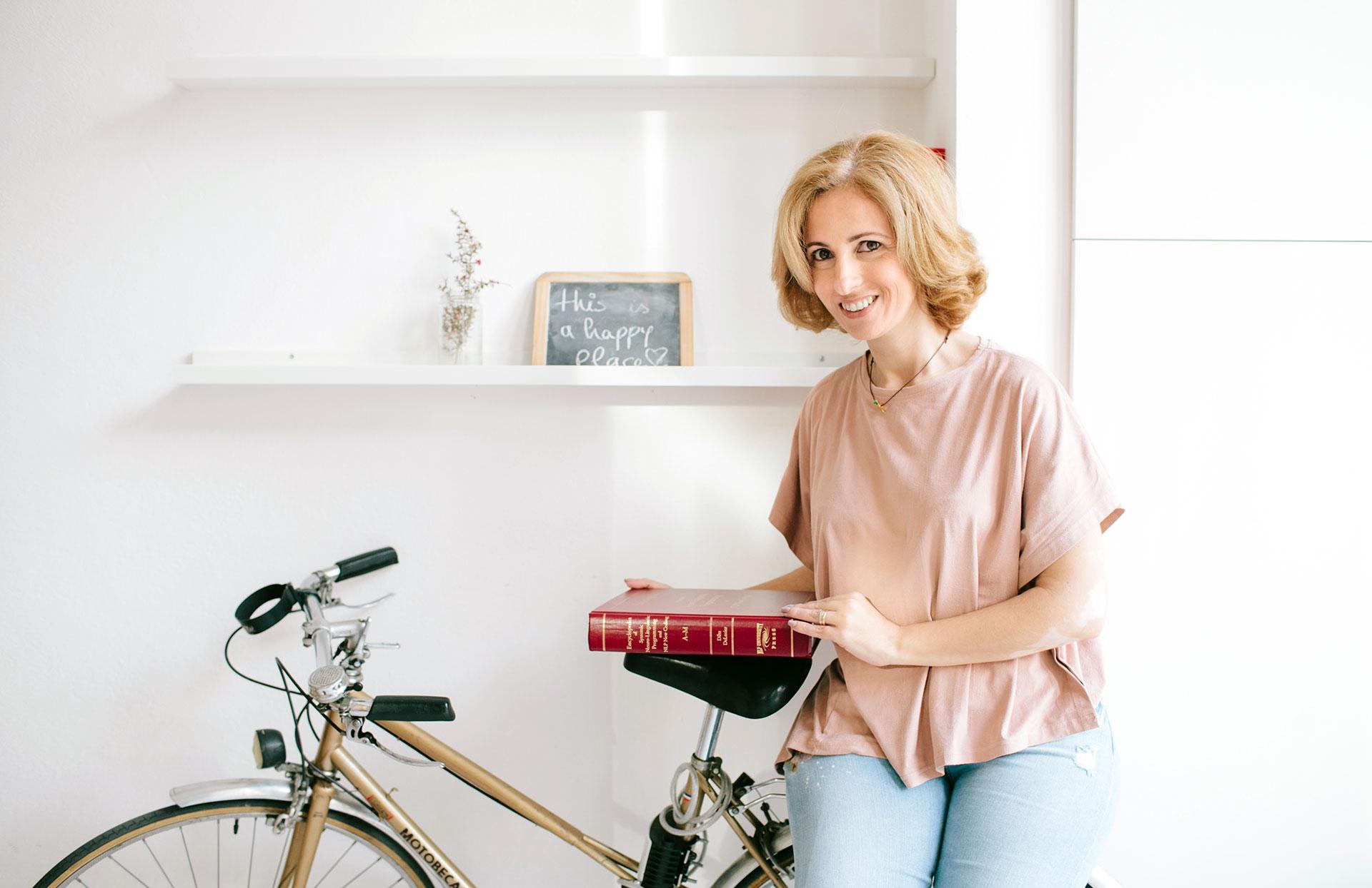 Rita Aleluia sentada numa bicicleta e com a enciclopédia sobre PNL nas mãos.