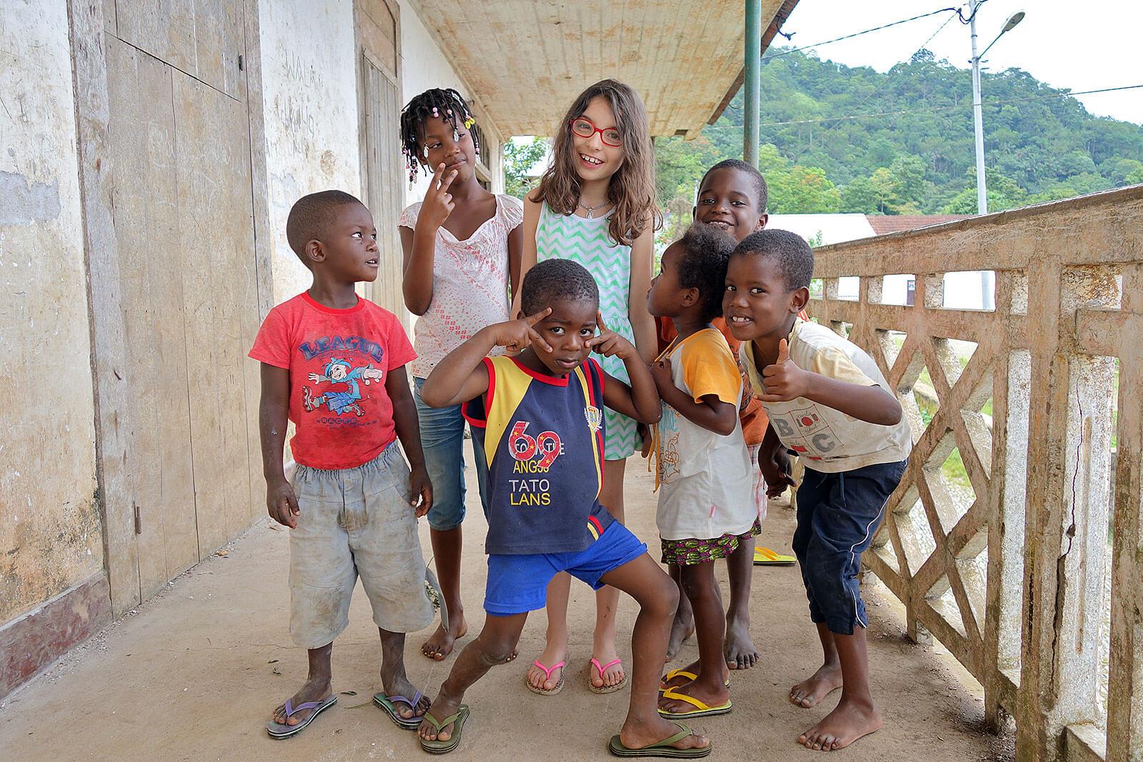 Menina caucasiana no meio de um grupo de crianças africanas.