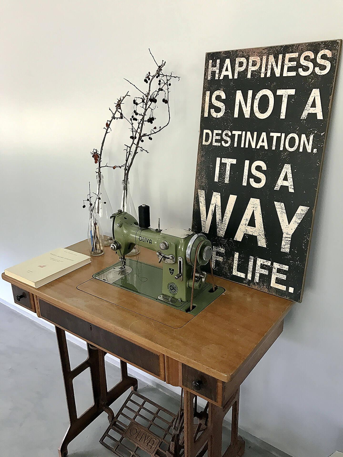 Máquina de costura antiga, junto a jarras com flores e quadro negro com citação.