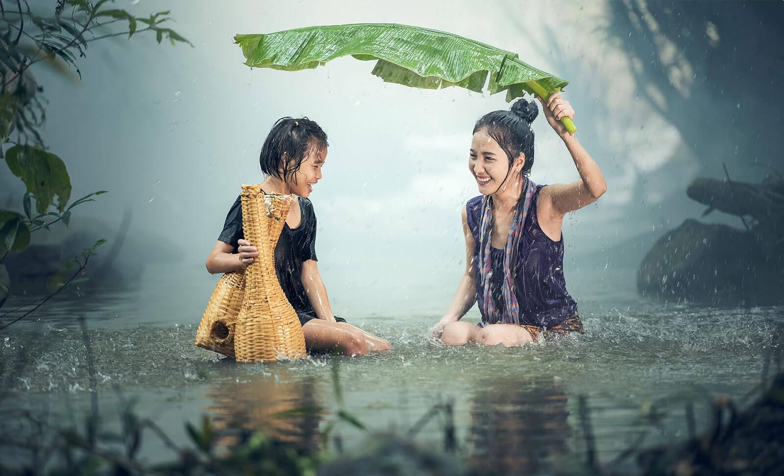 Mulheres asiáticas dentro de um rio, protegidas da chuva com folha de bananeira.