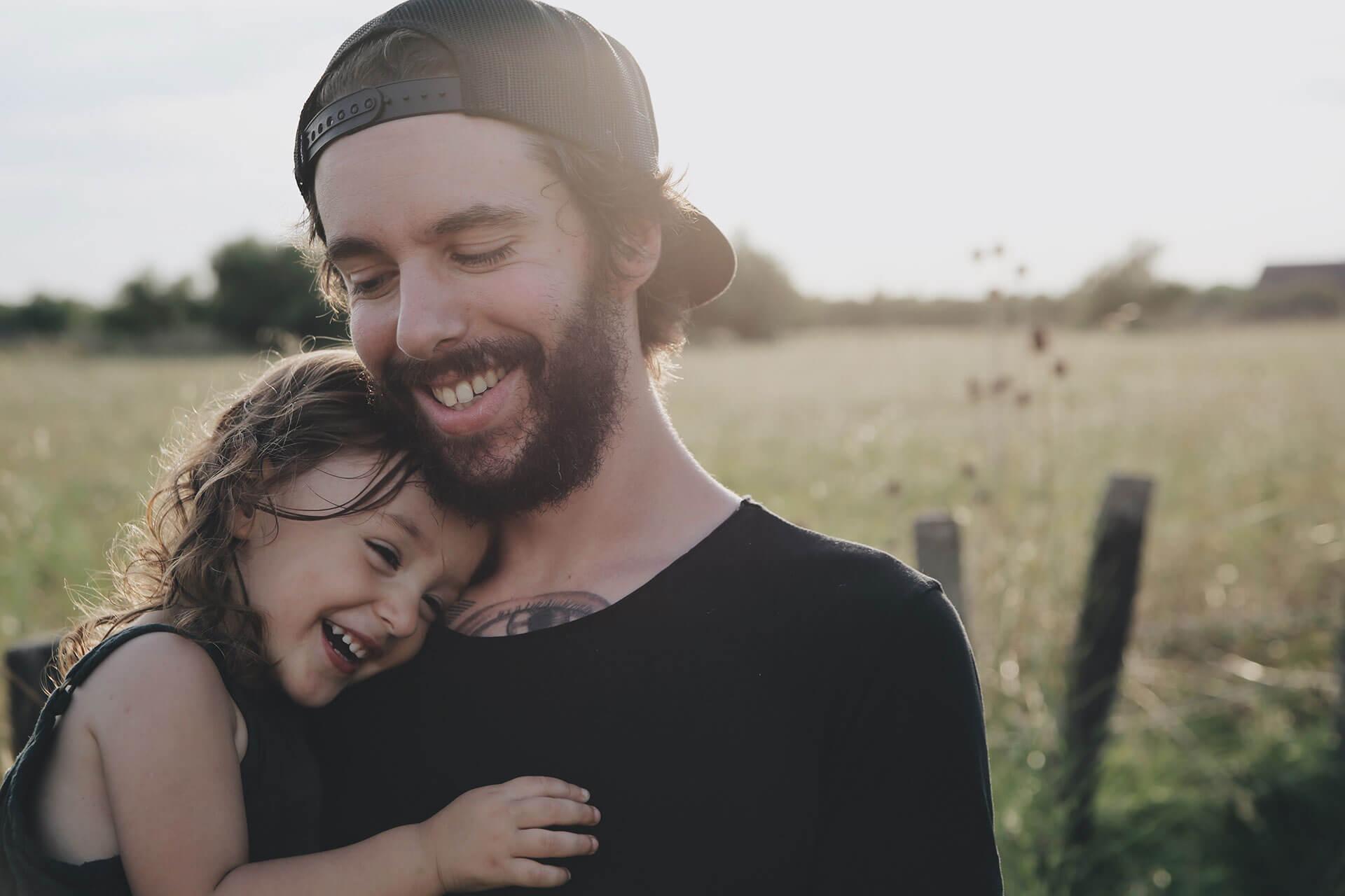 Pai com menina ao colo no campo.