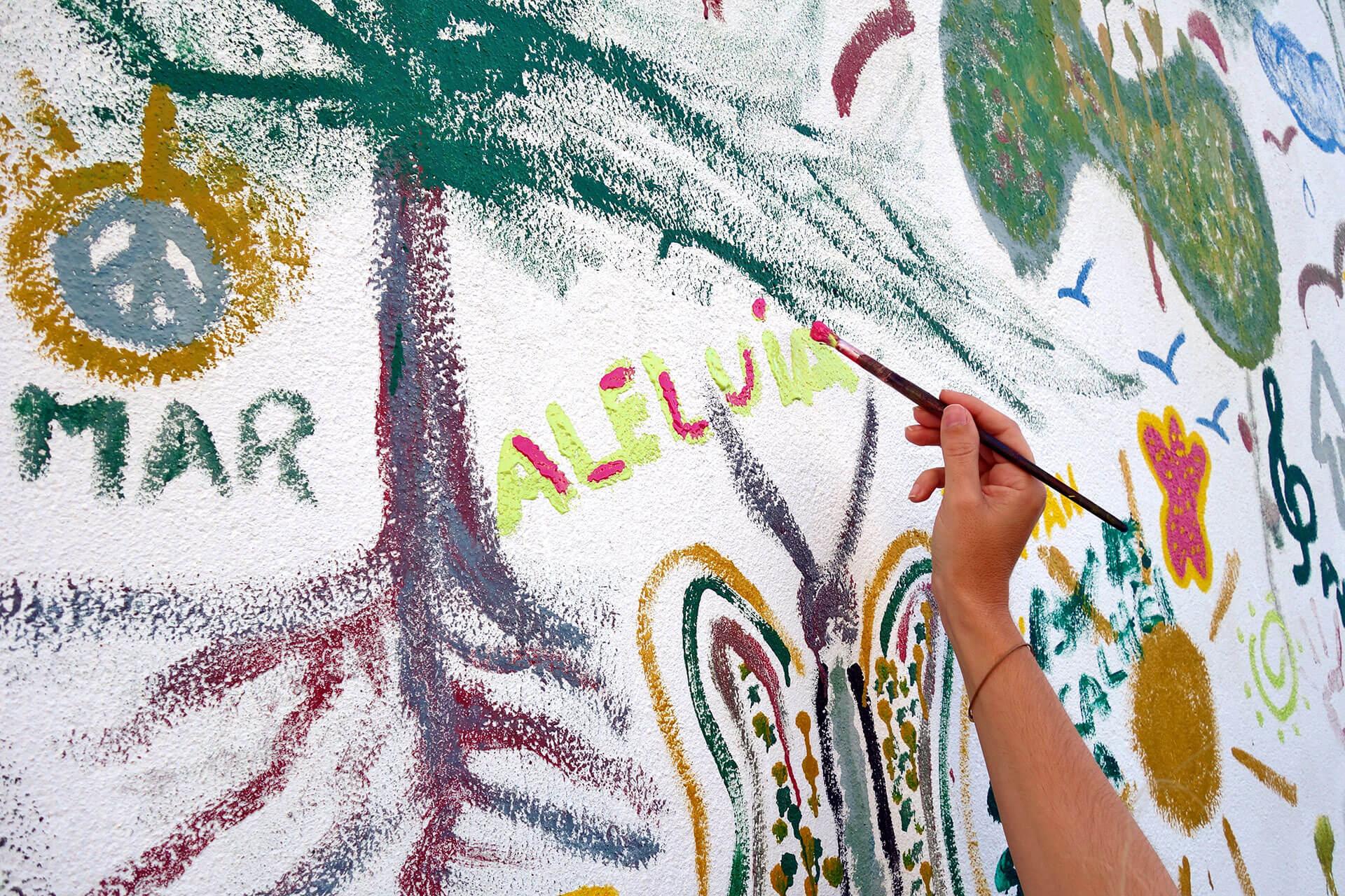 Mão segura num pincel para pintar parede com motivos relacionados com PNL