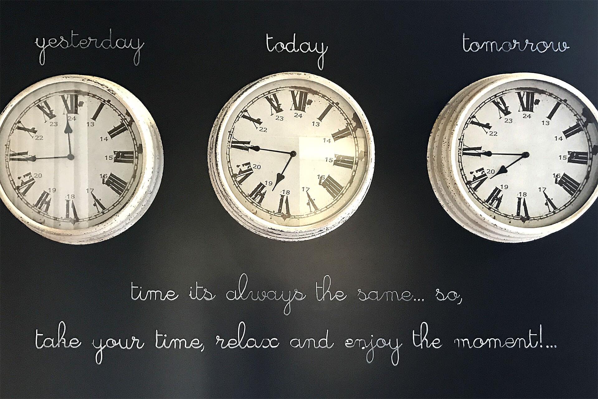 Relógios antigos numa parede negra, com palavras e citações escritas a giz