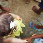 Menina com laço branco no cabelo a brincar com crianças africanas.