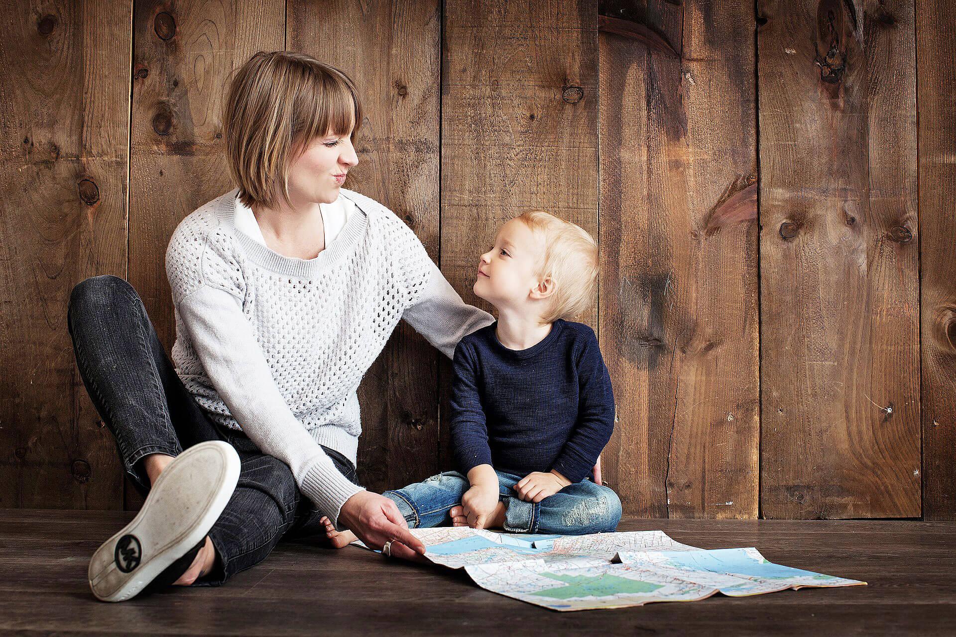 Mãe e criança sentadas no chão, encostadas a parede forrada com madeira e mapa no chão.