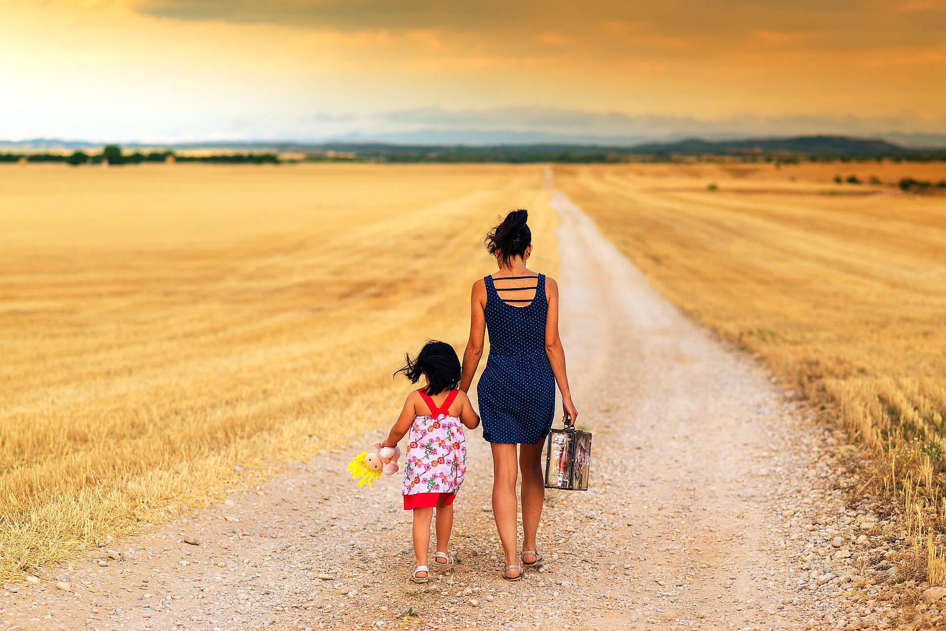 Mãe que transporta mala e criança com boneco na não, que caminham de mãos dadas através de um caminho de terra numa seara.