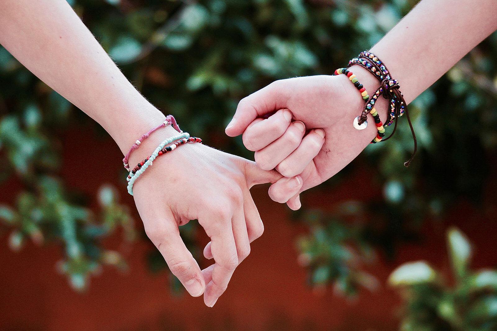 Pulseiras em braços com mãos dadas.