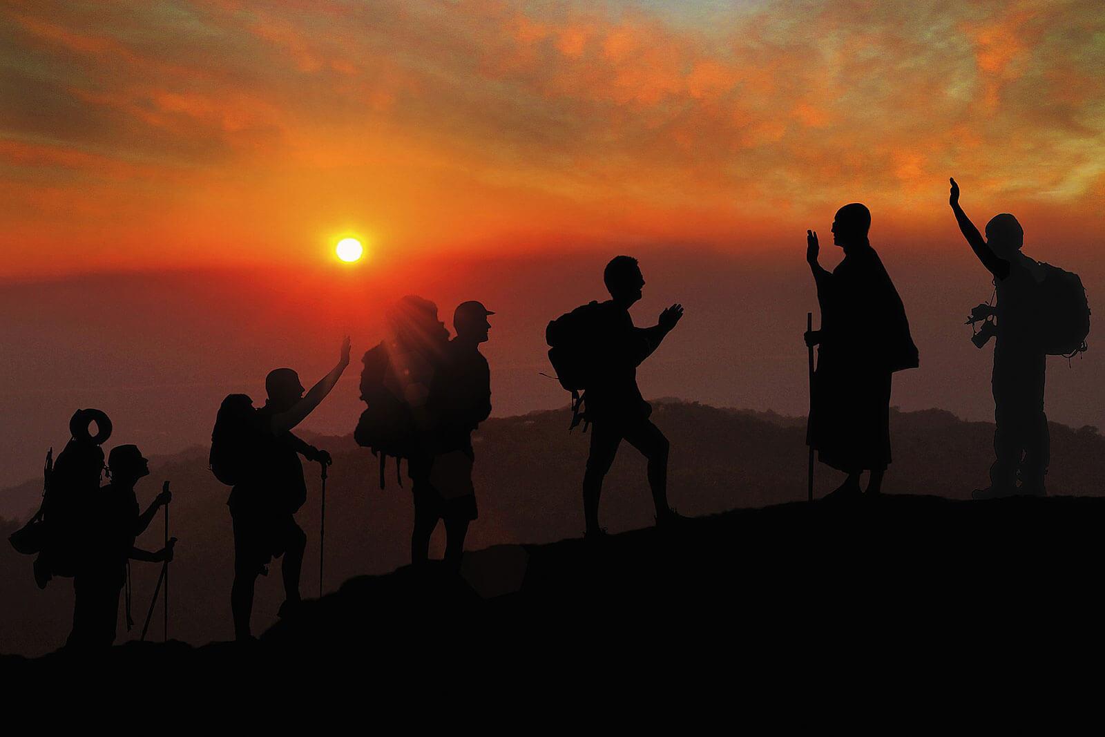 Montanhistas, no topo de uma montanha, em contraluz com o pôr-do-sol.