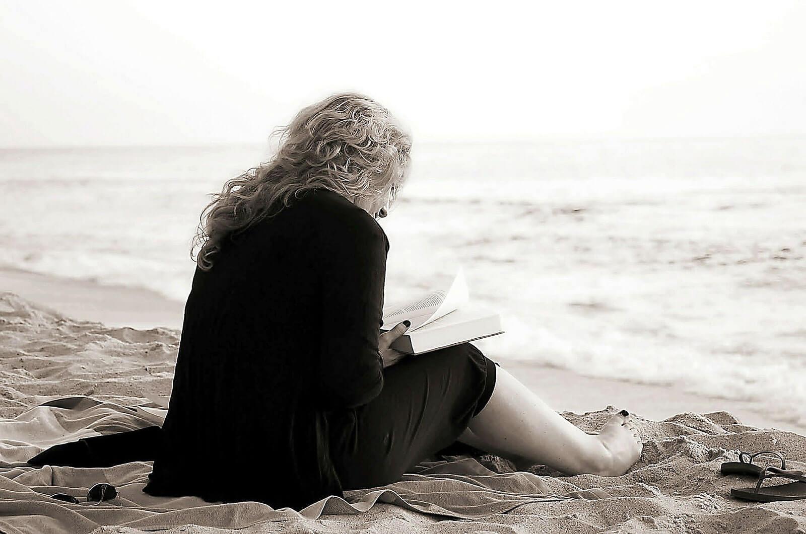 Mulher a ler um livro, sentada na areia, junto ao mar.