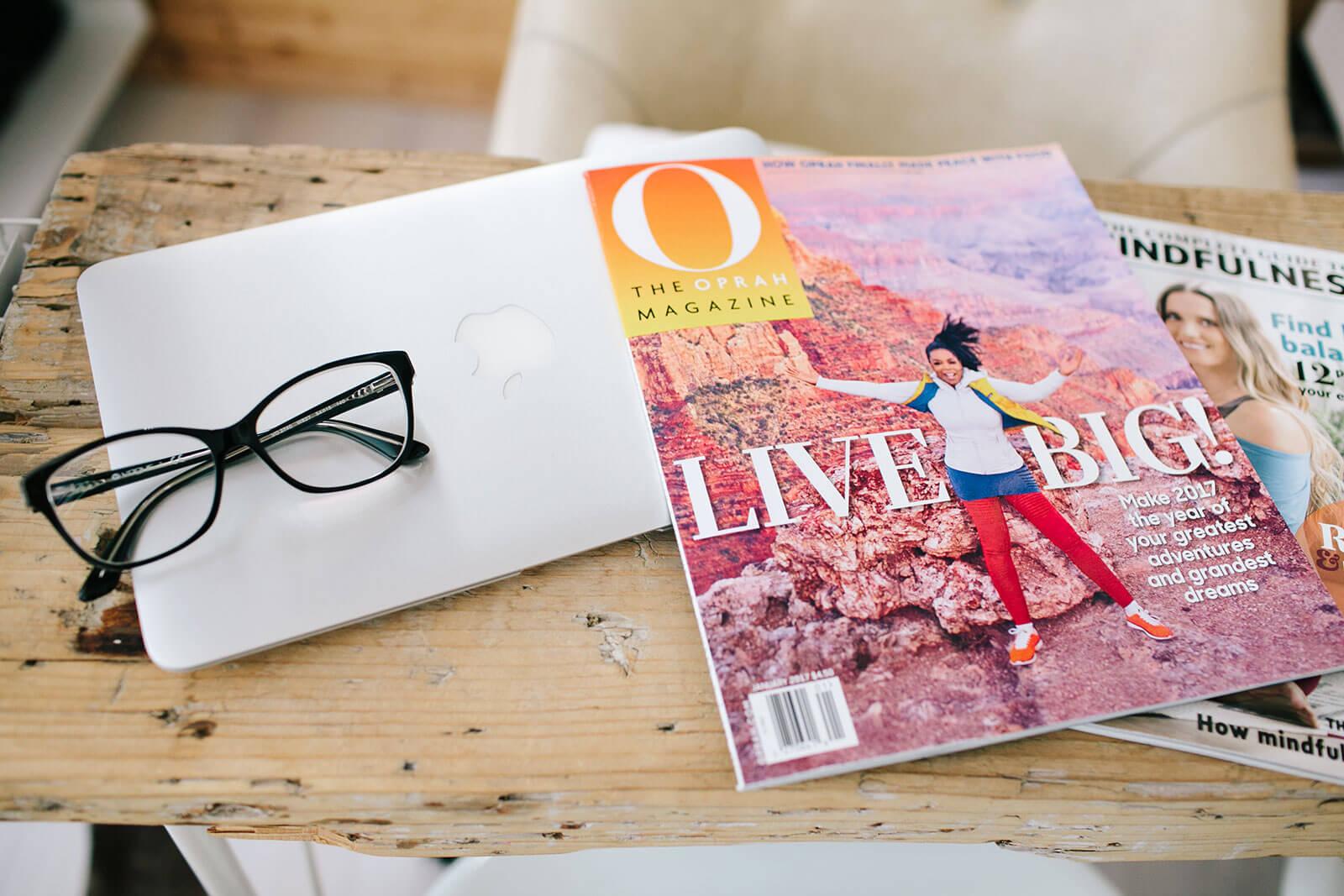 Revista Oprah, computador portátil e óculos sobre uma mesa de madeira.