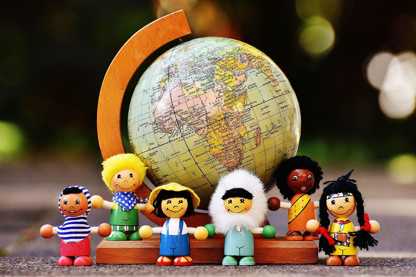 Bonecos de madeira, que simbolizam várias raças, junto a um globo.