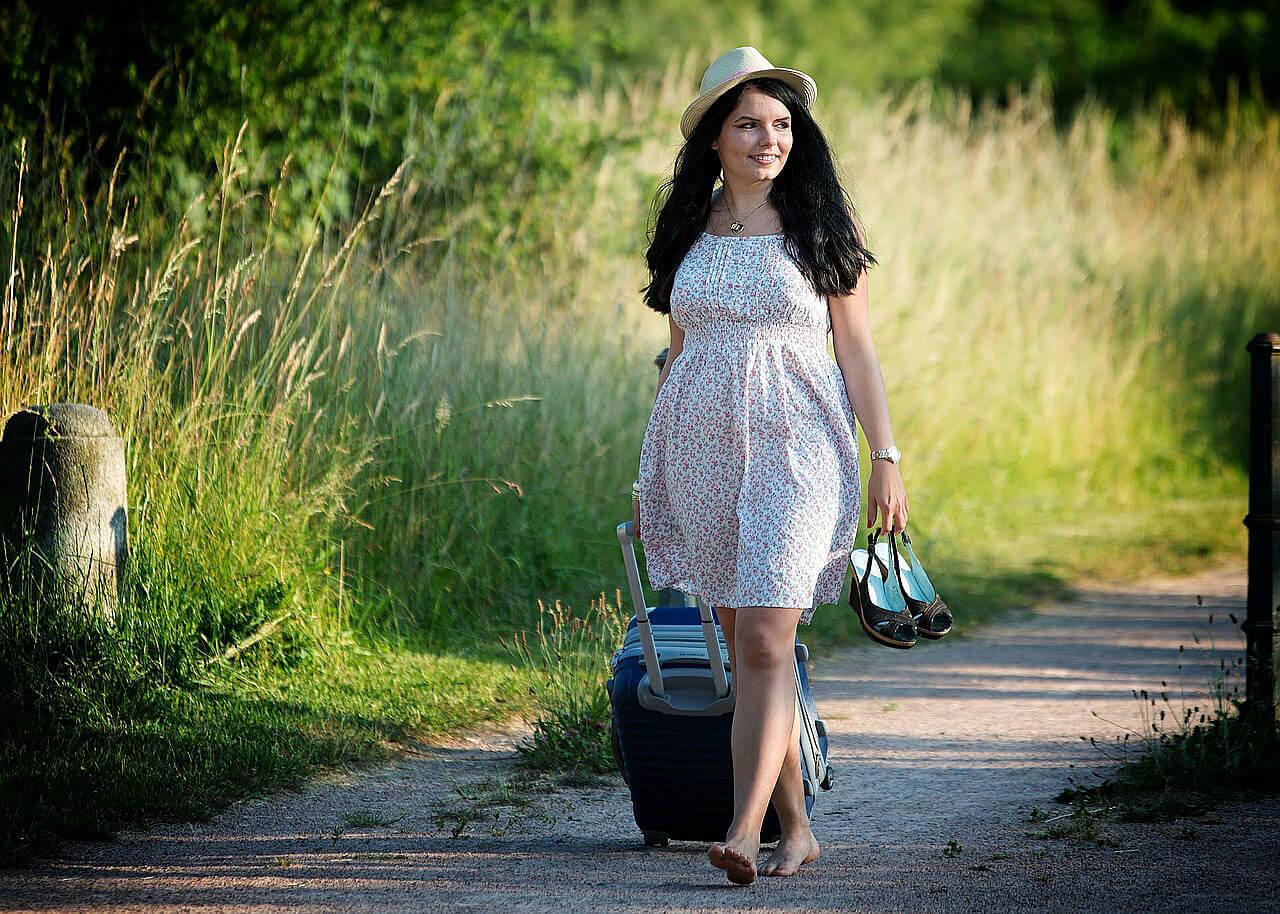 Rapariga descalça e com um chapéu, a puxar um trolley por um caminho de terra.