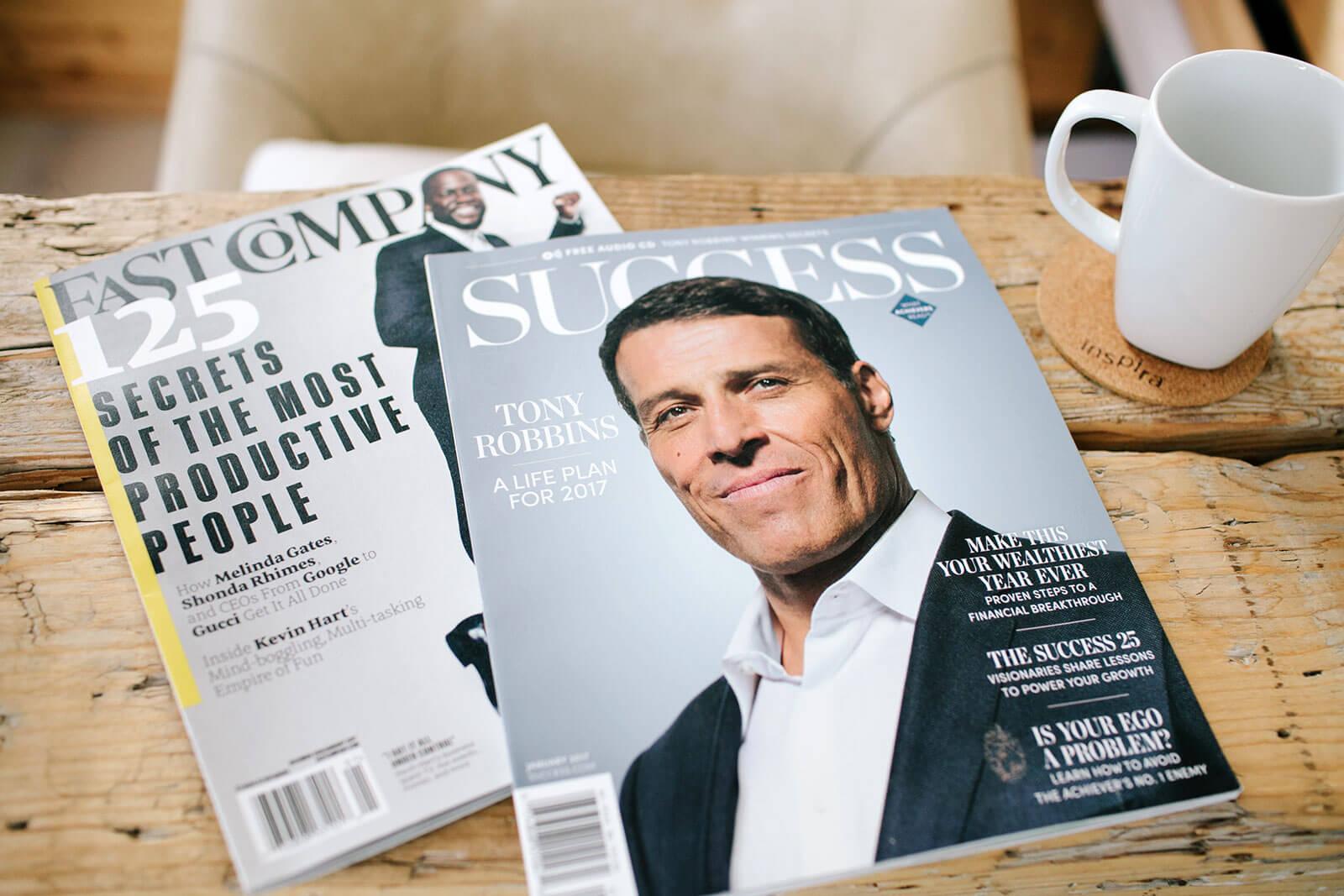 Revista Success sobre Tony Robbins sobre mesa de madeira.