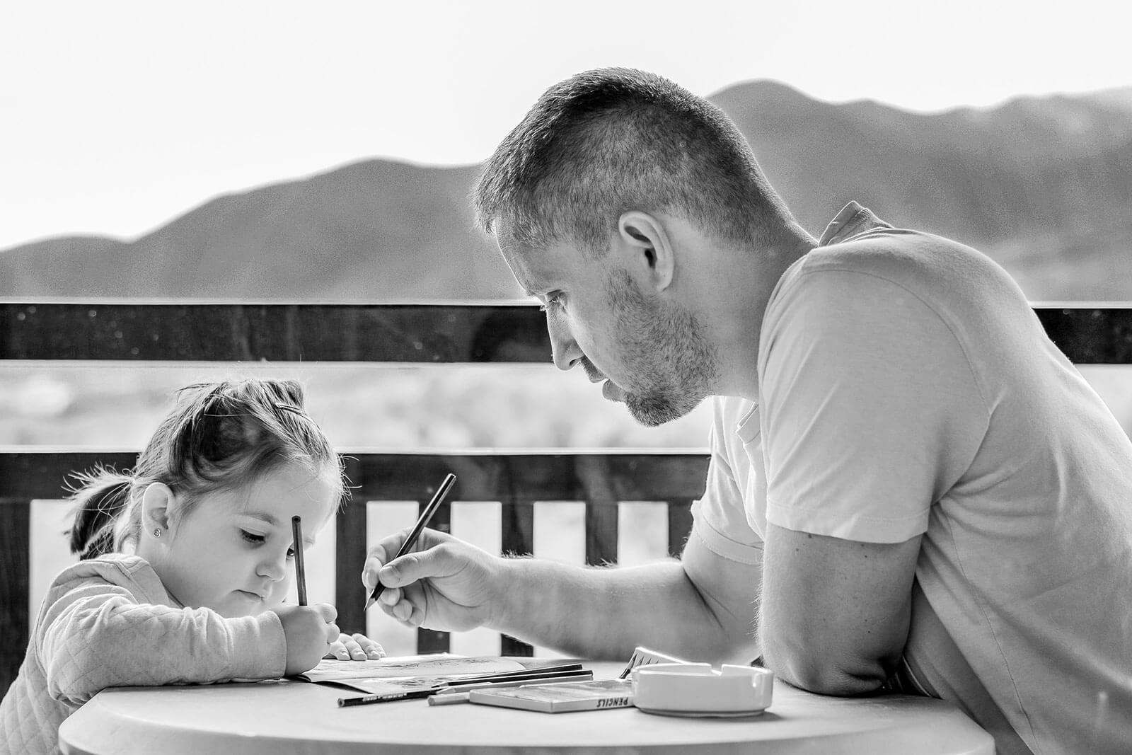 Pai e filha sentados à mesa, numa varanda, a escrever em cadernos.