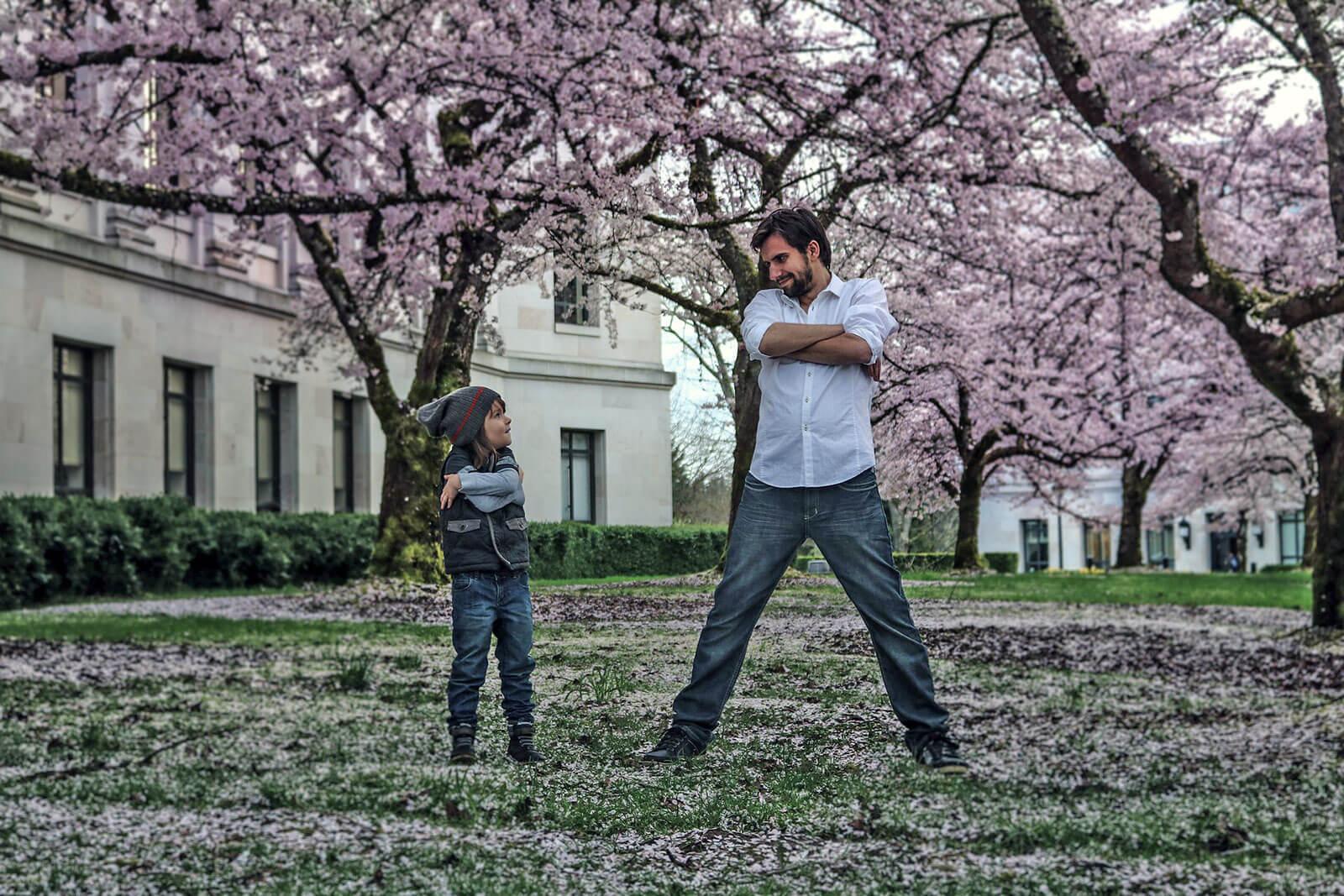 Pai e filho, de braços cruzados, num jardim com cerejeiras em flor.