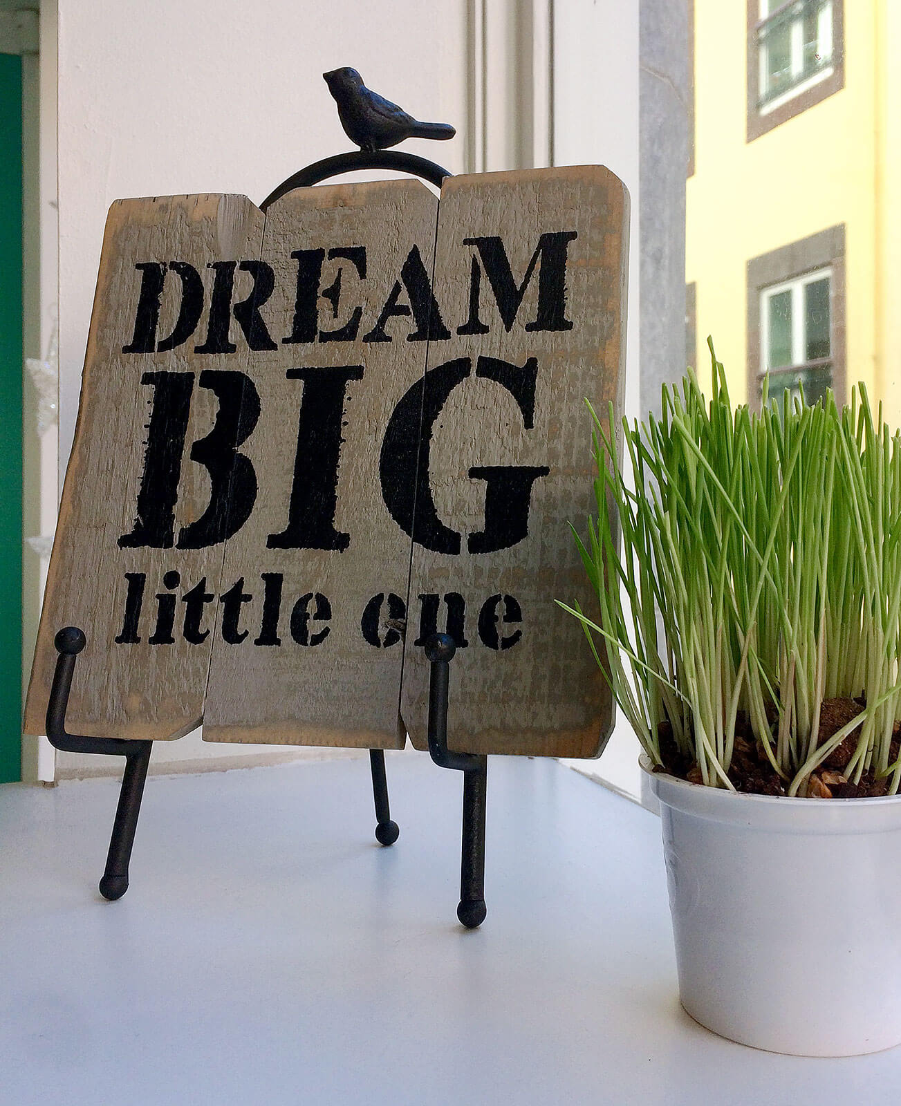 "Placard com texto ""Dream Big little one"" e vaso com planta junto a uma janela."