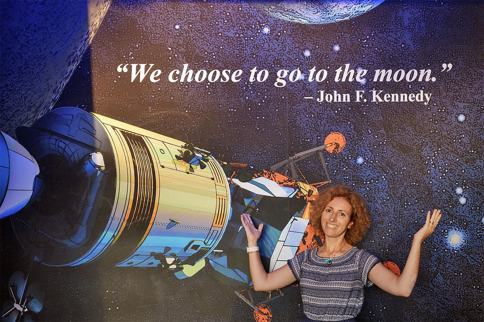Rita Aleluia junto a placard com satéllite no centro Kennedy, nos Estados Unidos da América.