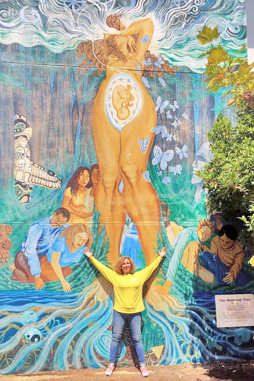 """Rita Aleluia frente a mural """"The Maternal Tree"""""""