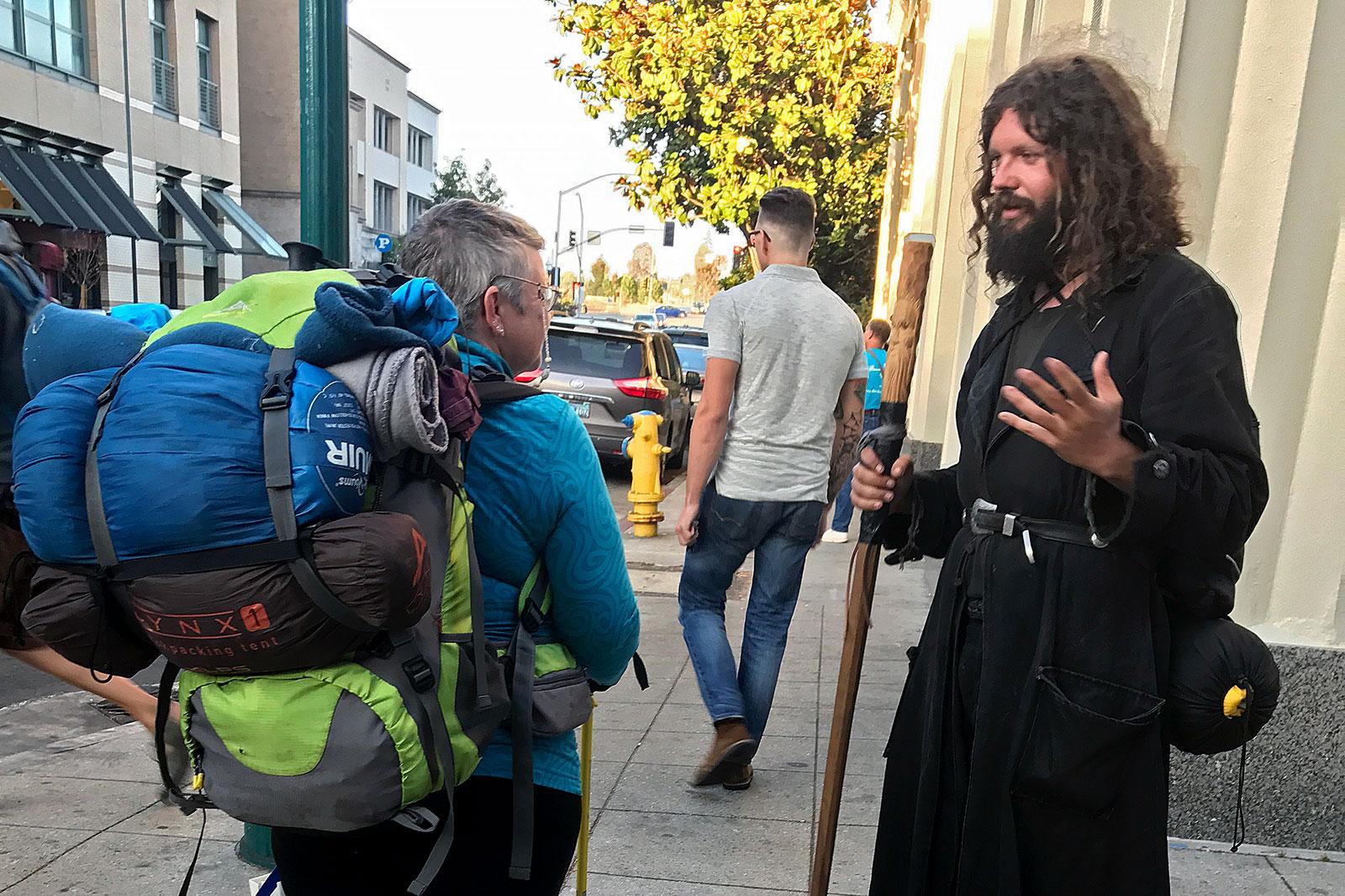Homem com aspecto de Jesus, falando com mochileiro na rua