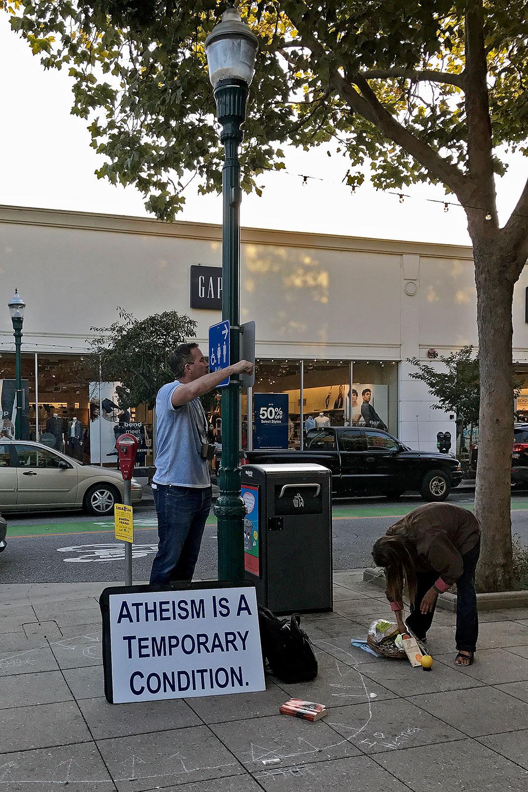 """Homens numa rua com placa """"Ateísmo é uma condição temporária"""""""