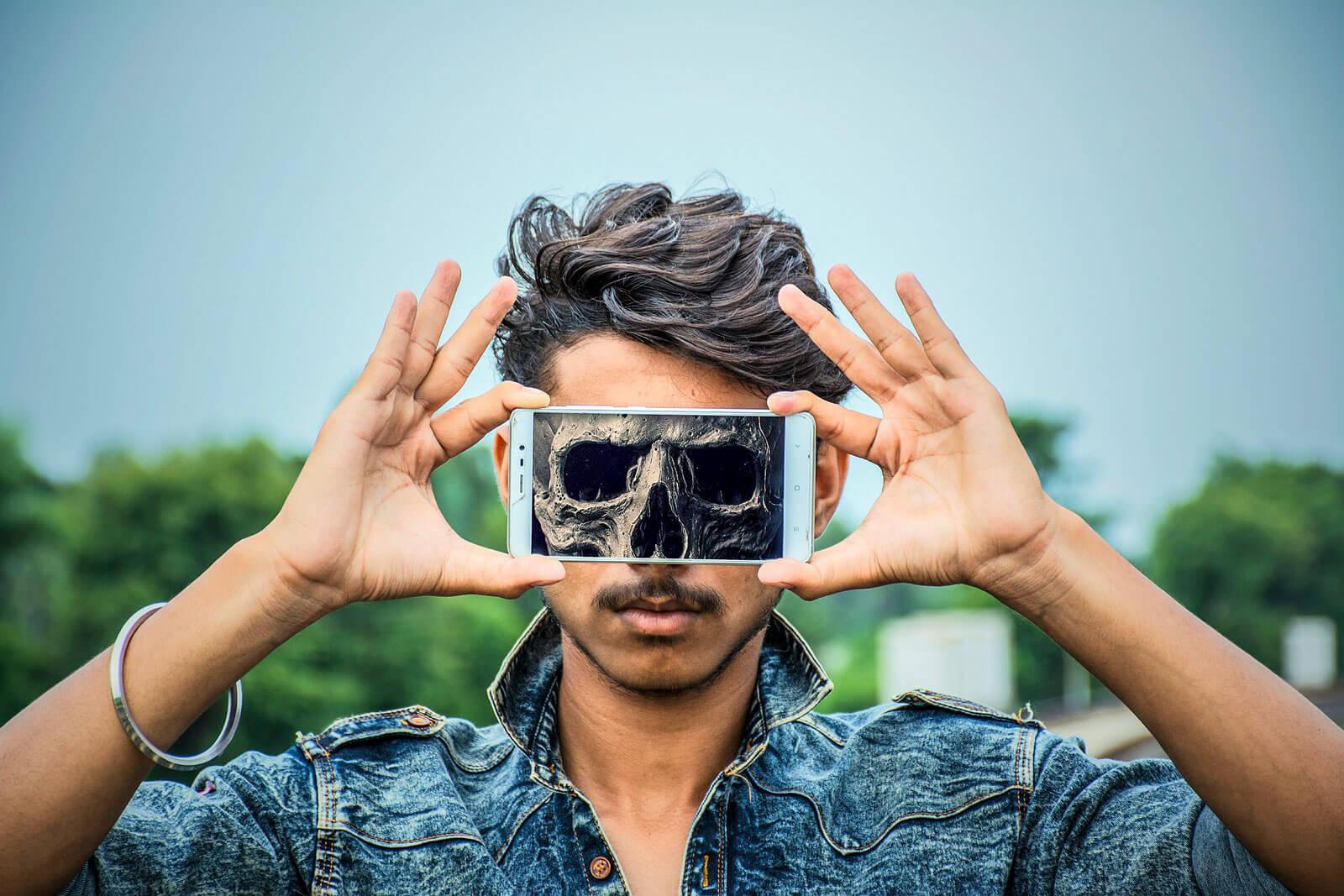 Rapaz com smartphone, à frente da cara, onde se vê uma imagem de uma caveira