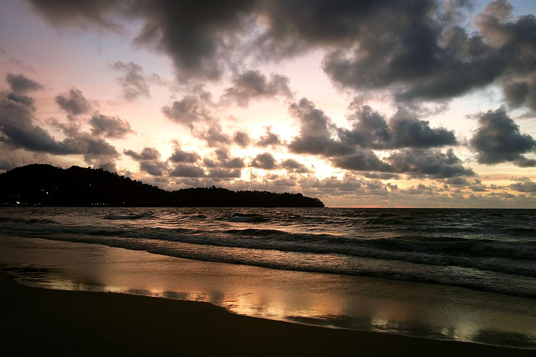 Mar junto a uma praia com pôr-do-sol