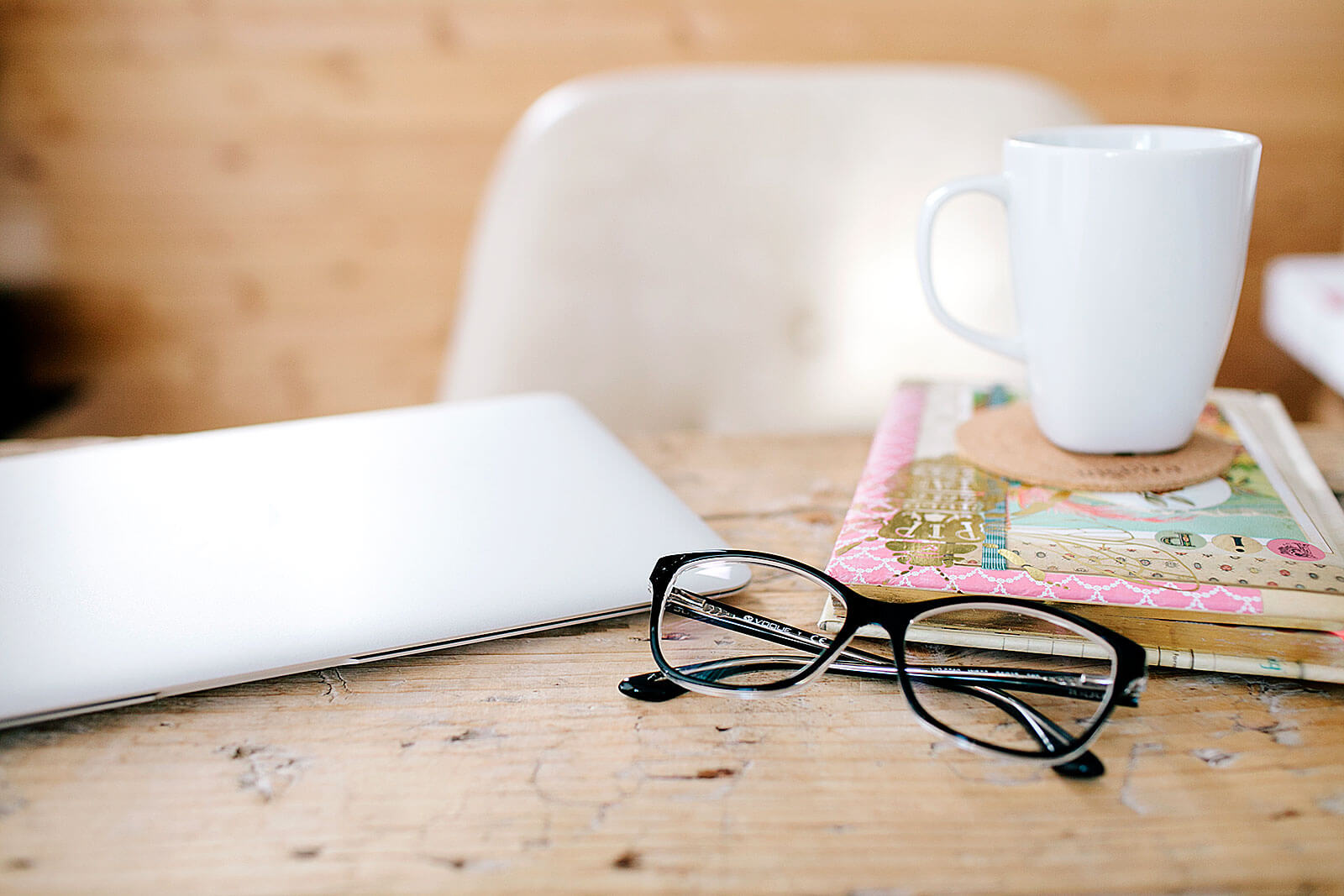 Mesa com computador portátil, óculos, caderno e caneca.