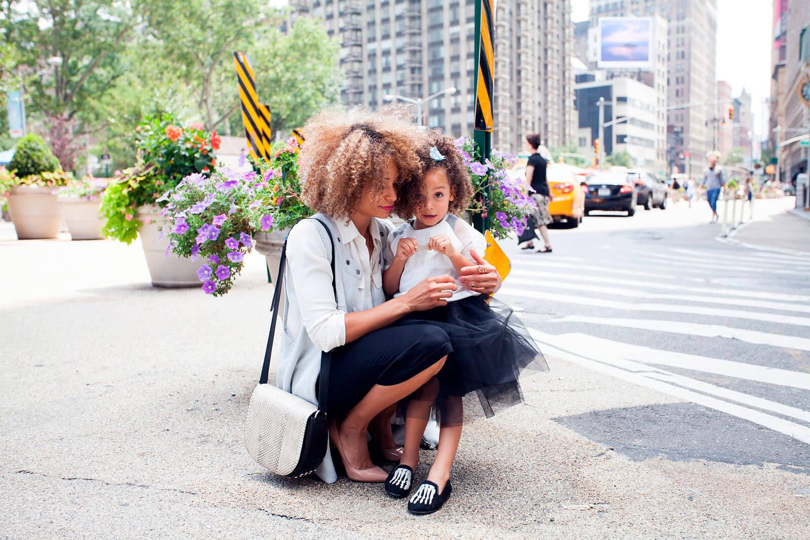 Mulher de raça negra com criança, junto à passadeira de uma rua cheia de prédios e vasos com vegetação.