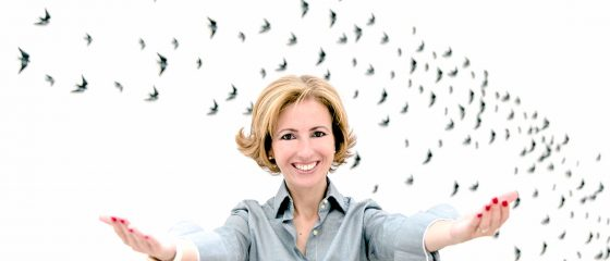 Rita Aleluia com os braços abertos, frente a uma parede com andorinhas.