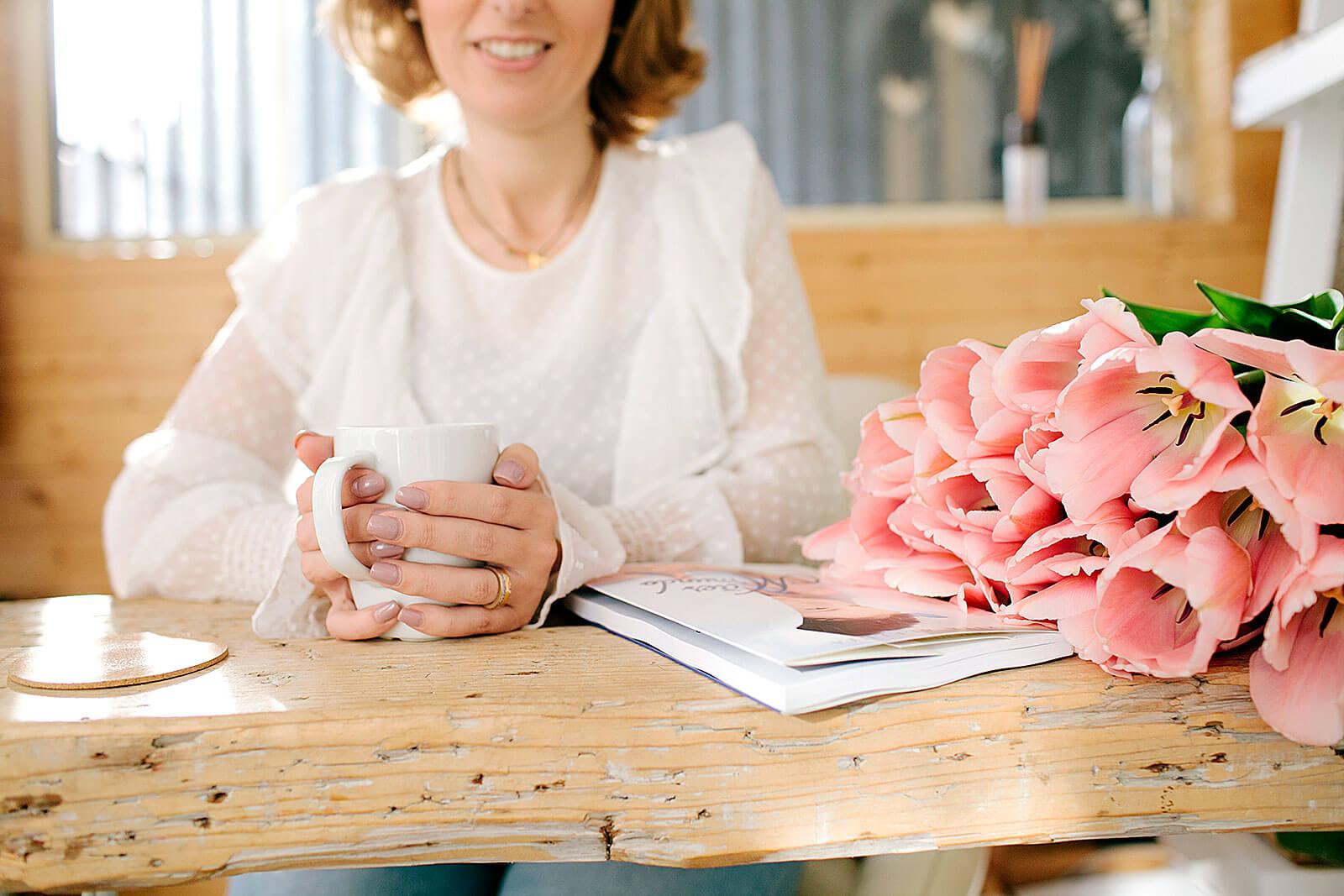 Rita Alelua com caneca, livro e ramo de rosas sobre uma mesa de madeira.