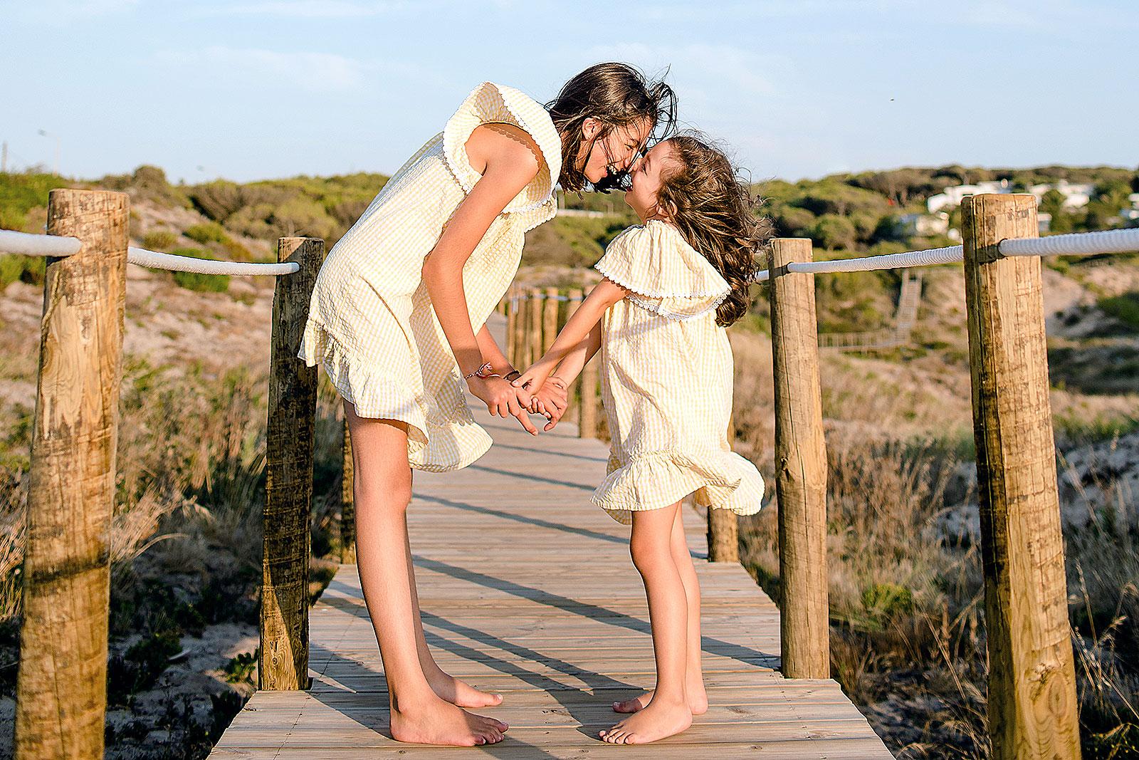 Crianças a abraçarem-se num passadiço de madeira junto a uma praia.