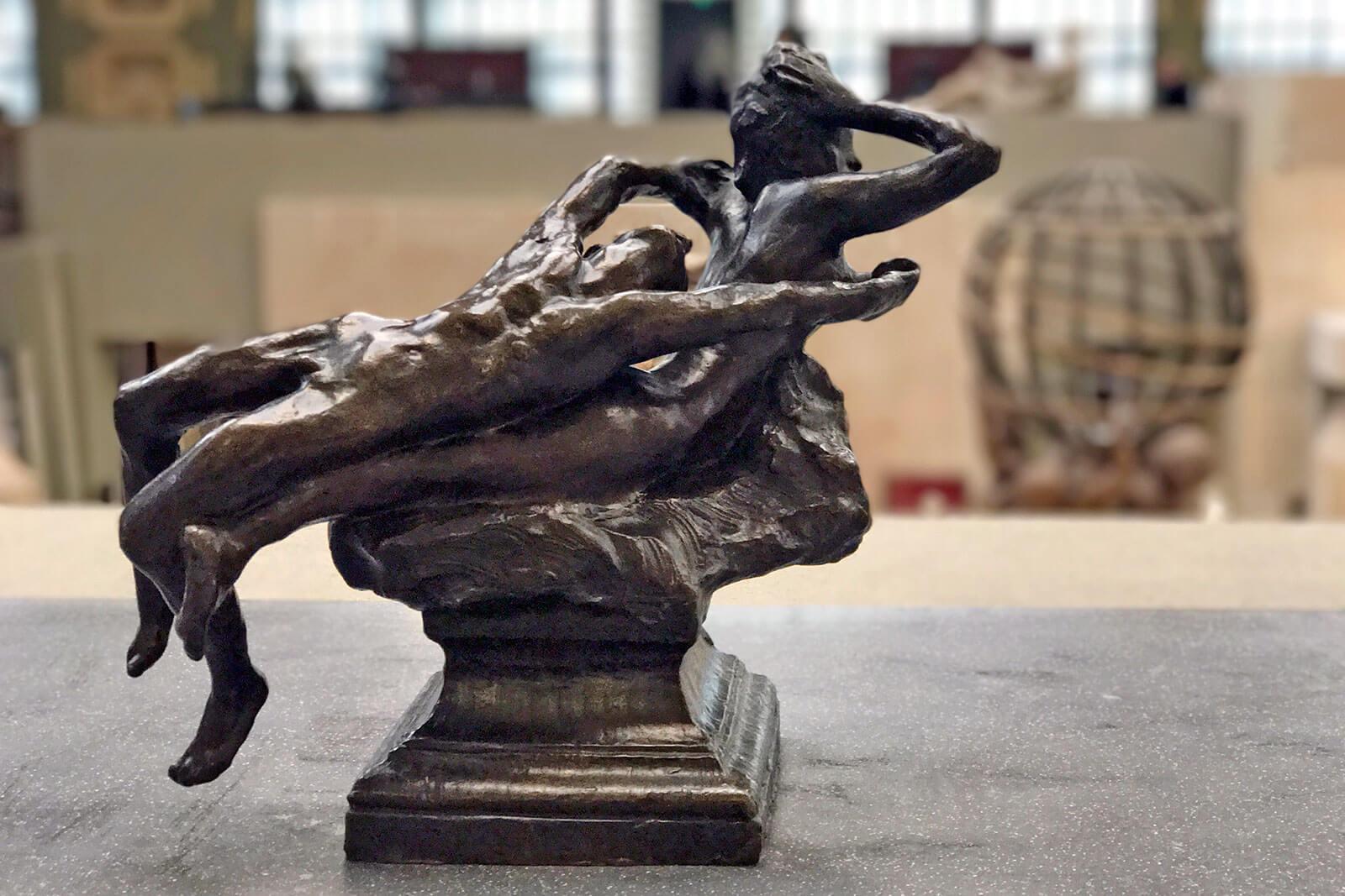 Escultura com dois corpos entrelaçados.