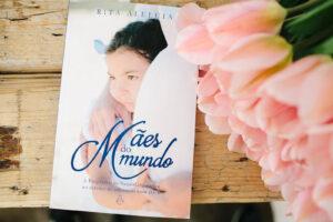 """Livro """"Mães do Mundo"""" e ramo de túlipas sobre uma mesa de madeira rustica."""
