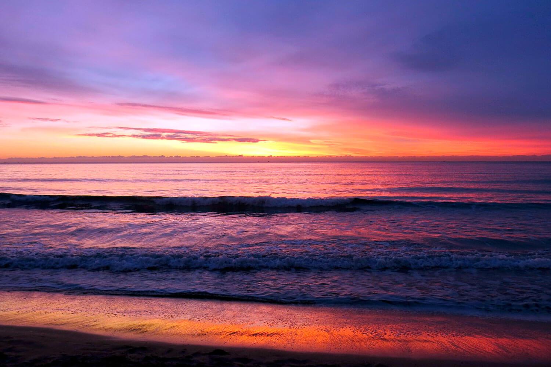 Tons laranja do pôr-do-sol numa praia com ondulação serena
