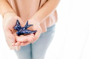 Mãos a segurar numa uma andorinha de porcelana azul