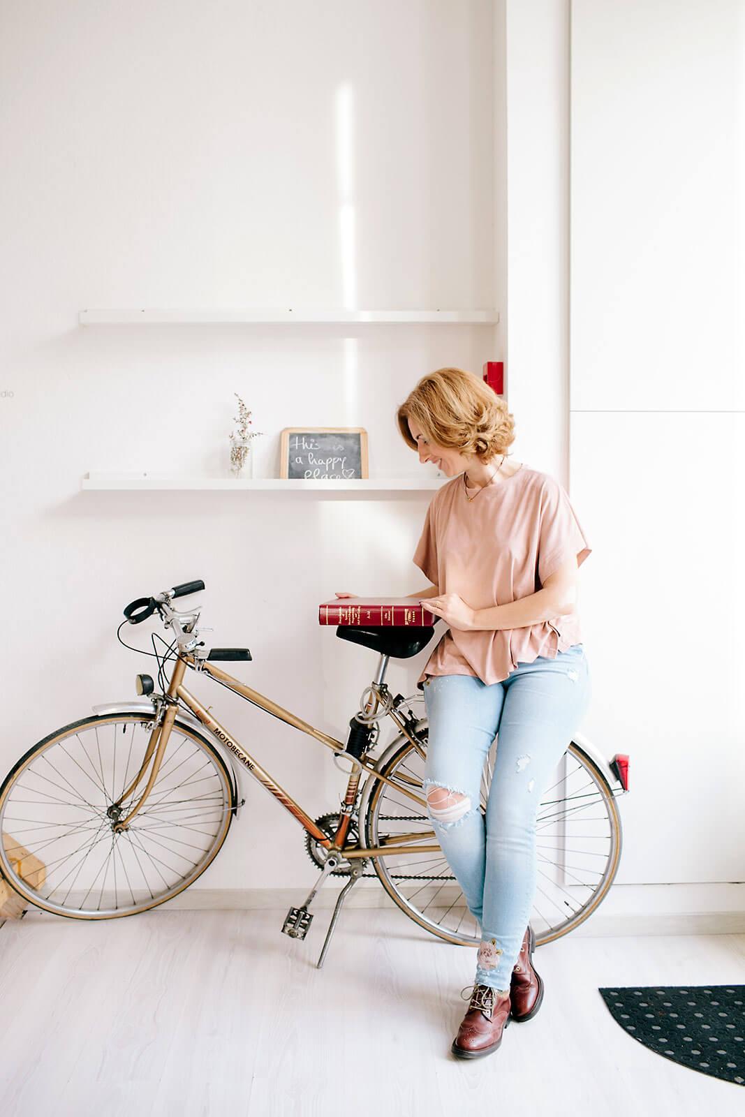 Rita Aleluia sentada numa bicicleta, segurando na enciclopédia de PNL.