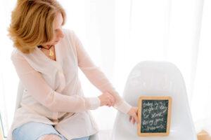 Rita Aleluia sentada a segurar um quadro de ardósia.