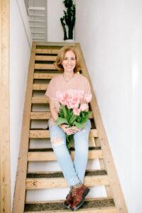 Rita Aleluia sentada numas escadas de madeira, com um ramo de túlipas nas mãos.