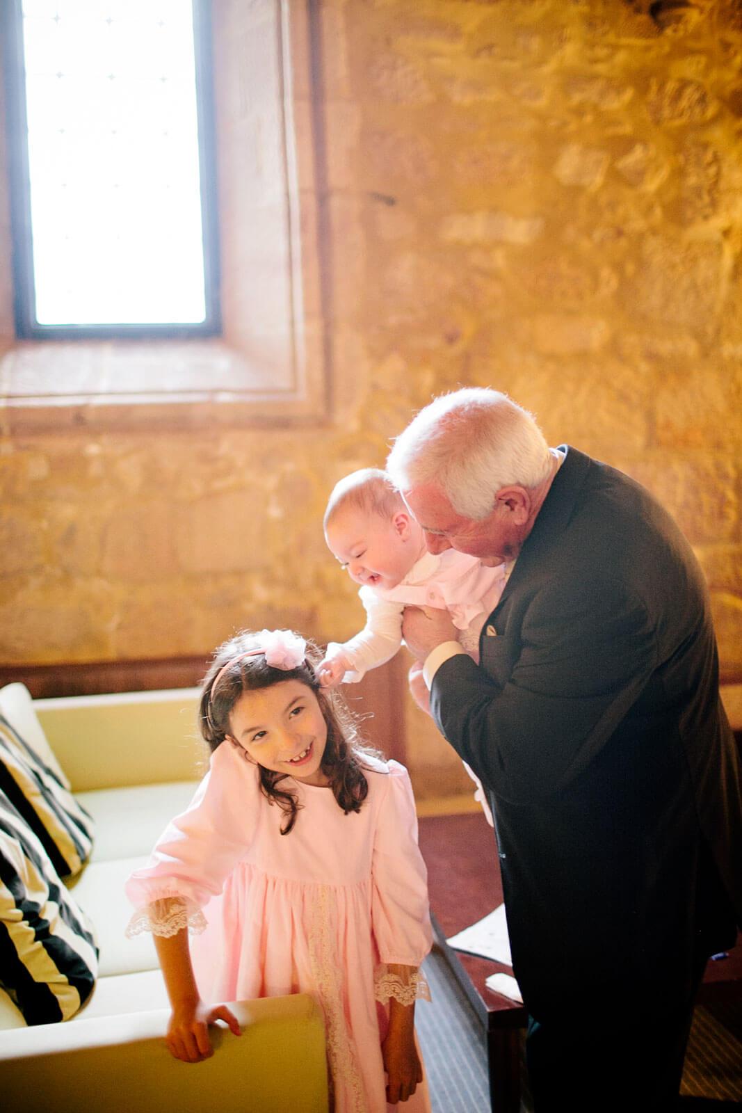 Avô e netas numa sala com paredes de pedra.
