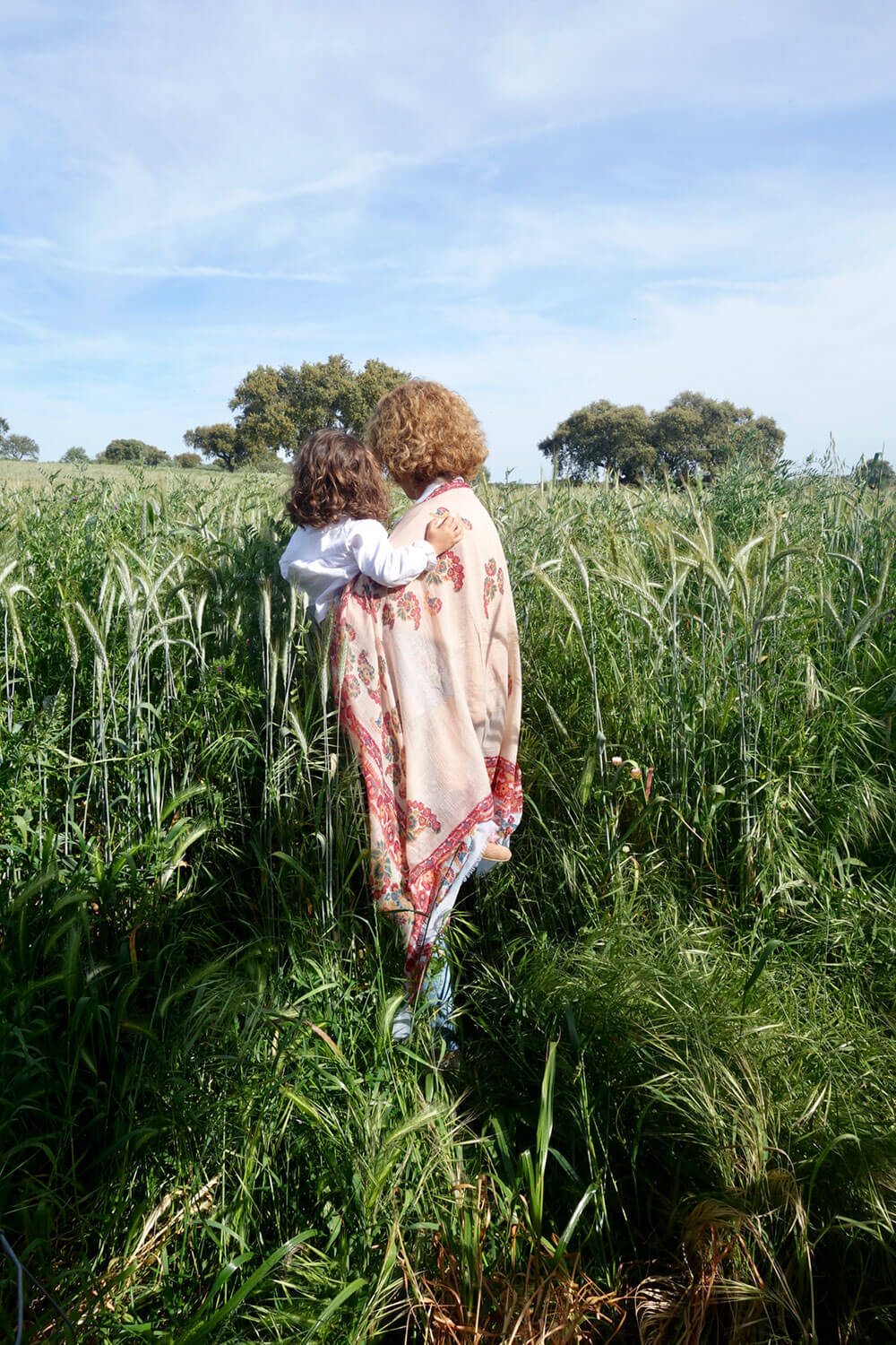 Child on mother's lap in the middle of a green wheat field.