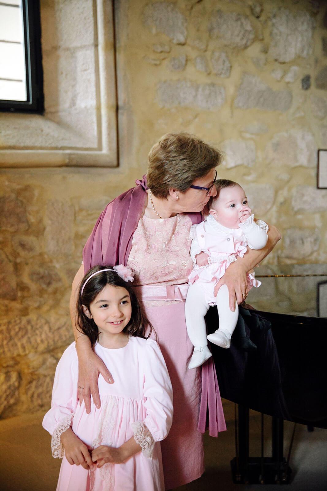 Avó e filhas da Rita Aleluia numa sala com paredes de pedra e um piano.